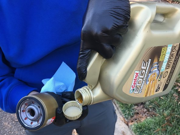 Pour a small amount of oil into the lid of the oil bottle.