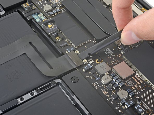 Use a spudger to disconnect the trackpad ribbon cable by gently prying its connector straight up from the logic board.