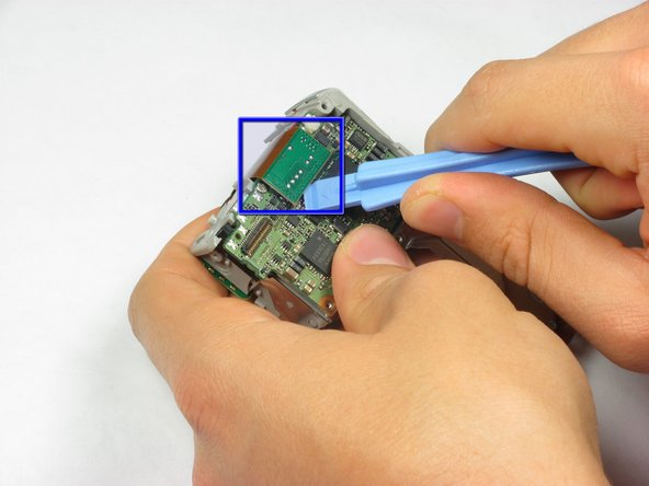 Use a spudger or a flathead screwdriver to release the motherboard cable.