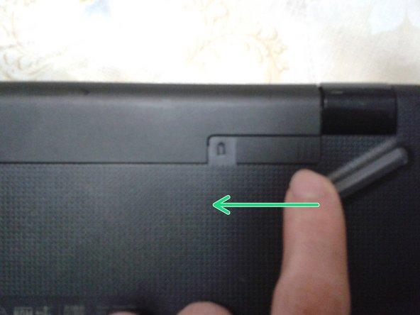 Desliza el seguro de batería derecho hacia la izquierda