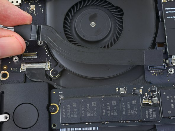Peel the I/O board cable up from the adhesive securing it to the fan.