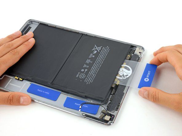 Remove the card and again slide it under the top edge of the battery, near the center.