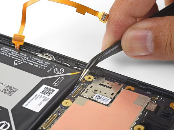 Find the second stretch-release adhesive's pull-tab at the upper left corner of the battery.