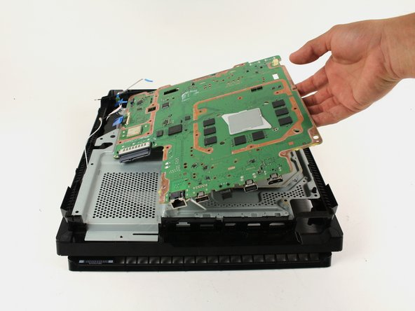 Grip the edge of the motherboard and slowly lift upwards to remove it from the device.