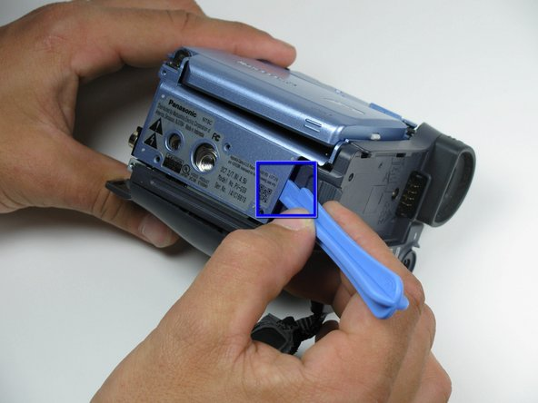 Place a plastic opening tool under the bottom of the blue panel beneath the camcorder.