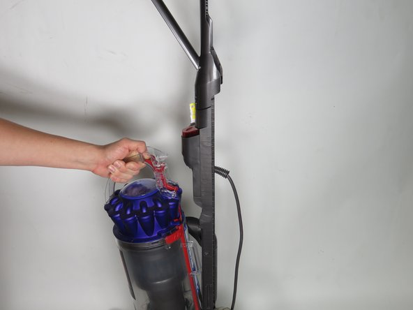 Remove the main canister by pressing the red release button and pulling up and away.