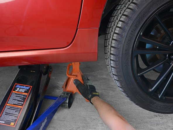 Slide your jack stand(s) into place near the jack, beneath a secure area of the vehicle's frame.