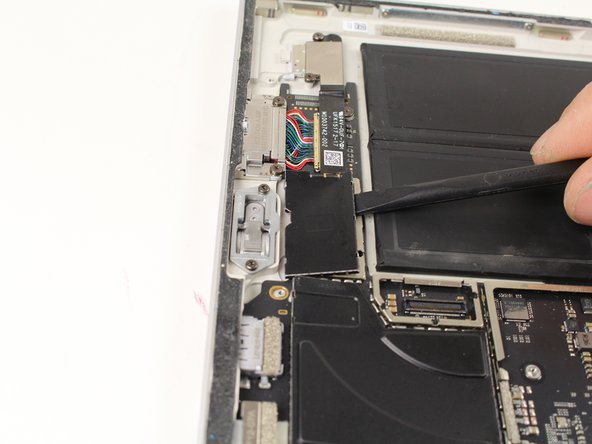 Pry up the metal cover on the motherboard using either the nylon spudger or plastic opening tool.