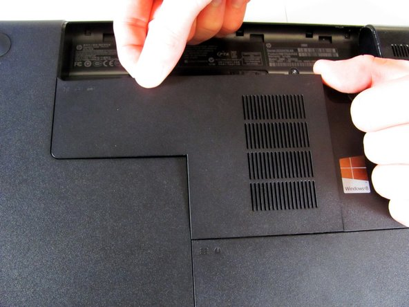 Once the screw is sufficiently loosened, gently unclip the RAM compartment cover from its slots in the plastic chassis.