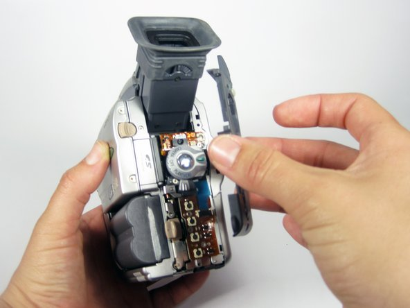 Remove the plastic cover from the rear of the camcorder by gently pulling it towards you while holding the camera as shown.