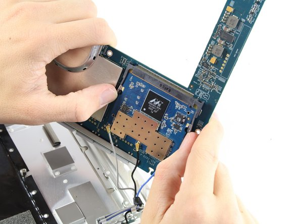 Pull the two indicated tabs away from the Wi-Fi Module and carefully pull out the card.