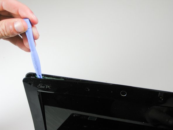 Use a plastic opening tool to disengage the plastic clips that secure the screen bezel to the display.