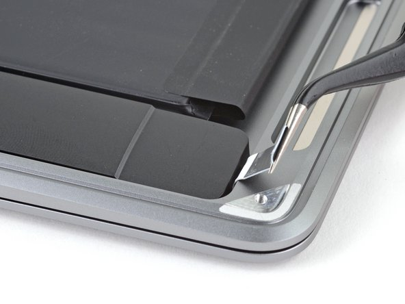 Use a pair of tweezers to lift up the black adhesive pull tab at the bottom of the right speaker, enough so you can grab it with your fingers.