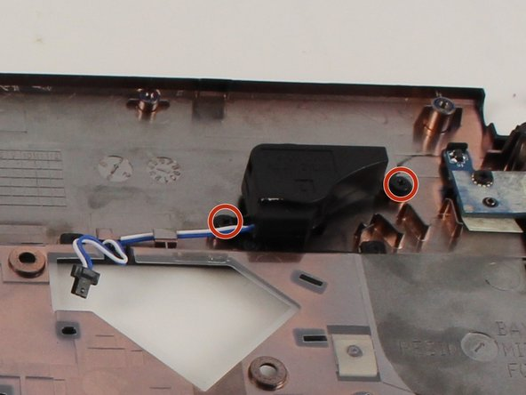 Locate and remove the two screws to loosen the speaker from the panel.