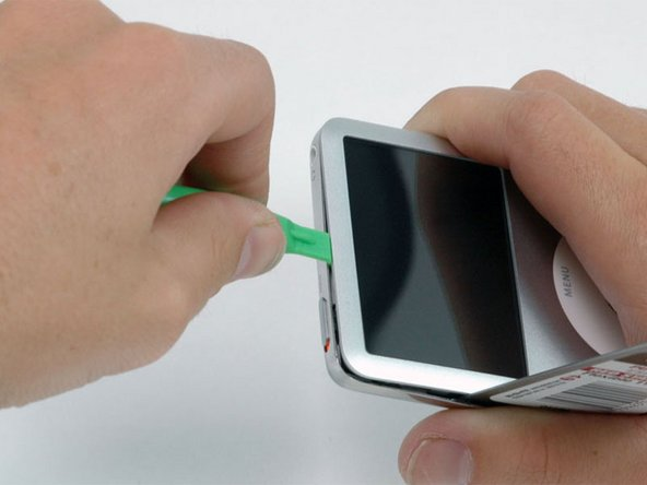 Between the lock slider and headphone jack, insert a plastic opening tool into the seam between the front and back of the iPod.