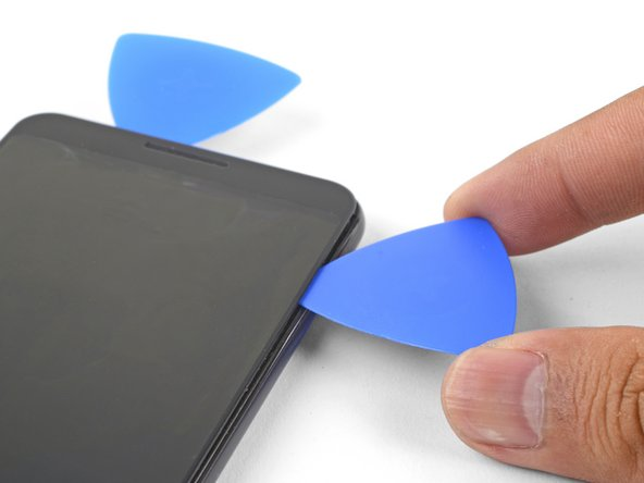 Continue heating edges with an iOpener and slicing the adhesive with an opening pick, until you've sliced through all of the adhesive.