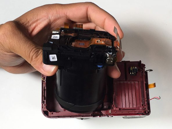 Pull the lens assembly from main body of the camera, using a spudger to pry if necessary.