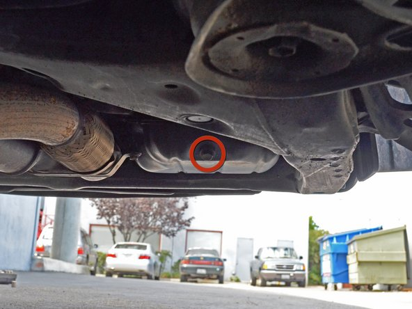 Locate the 14 mm hex oil drain plug. It will be on the passenger side of the car facing backwards.
