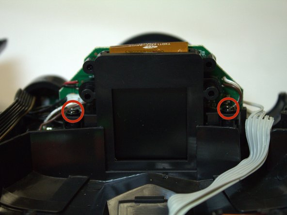 Remove the two black Phillips #0 screws that hold down the camera & display screen assembly.