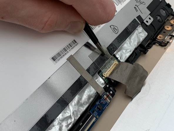 Using the Blunt Tweezers, remove the clear tape over the LCD Display connector.