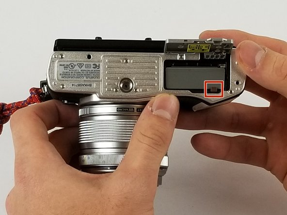 Move the dark red latch towards the direction of the camera lens to release the battery from the camera.