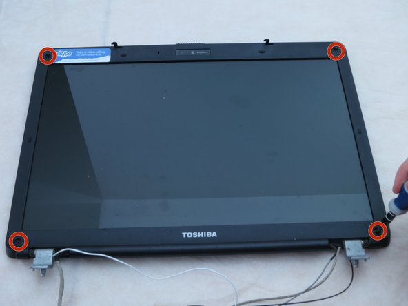 Using a Phillips #1 screwdriver, remove the four 4-mm screws at the corners of the screen.