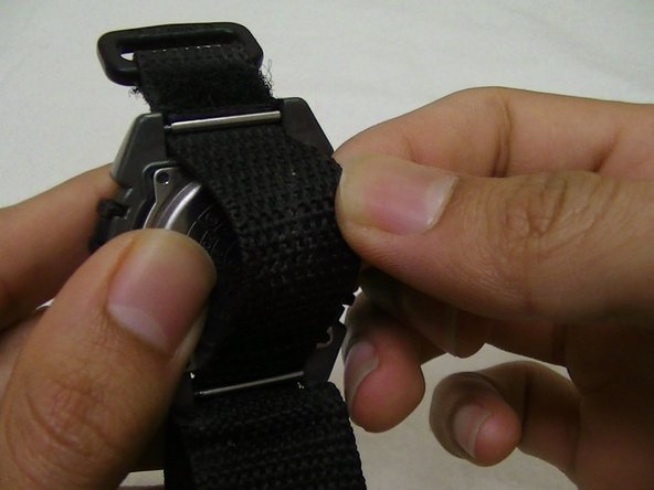 Pull back on the strap, while keeping a finger pressed to the metal covering.