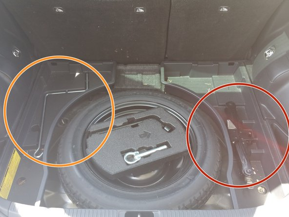 Locate the manufacturer supplied jack and jack handle in the spare tire compartment, these will be needed for the replacement.