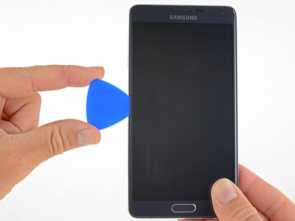 Slide the opening pick along the left edge of the display to separate the adhesive underneath.