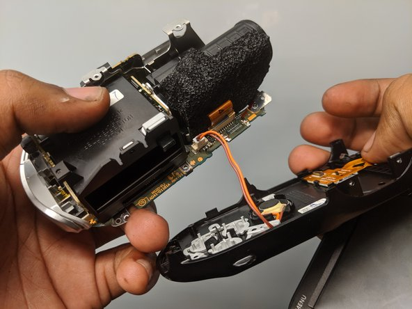 Pull apart the sides of the camera once the screws are removed.