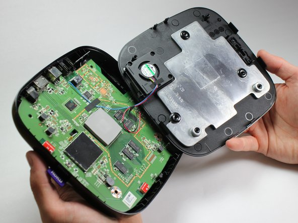 After you have created a gap large enough to fit your fingers between, gently lift up the top cover to open the device and reveal the motherboard.