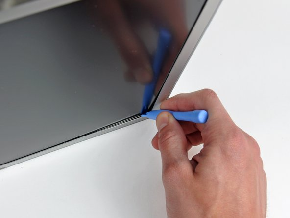 Insert a plastic opening tool between the metal LCD frame and the front bezel.