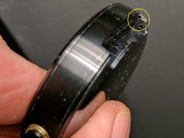 Locate the rectangular end of the fastener inside the wrist strap mounting pocket.
