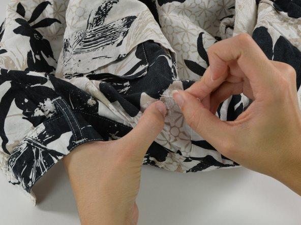 La toile est à présent collée, mais pour s'assurer qu'elle ne se décollera pas au bout de quelques lavages, il vaut mieux en coudre le bord au tissu.