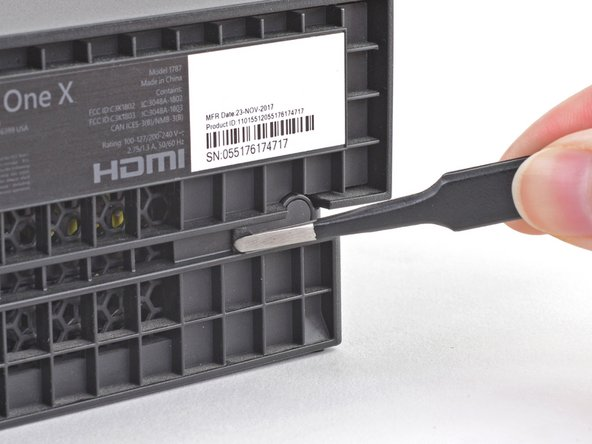 Use blunt tweezers to peel off the sticker covering the right-side screw on the back of the console.