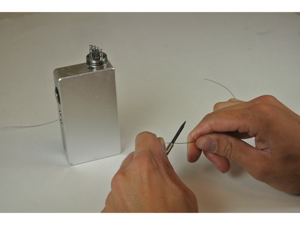 Hold the screwdriver and the wire end in one hand (non dominant) and the loose end of the wire in the other hand (dominant).