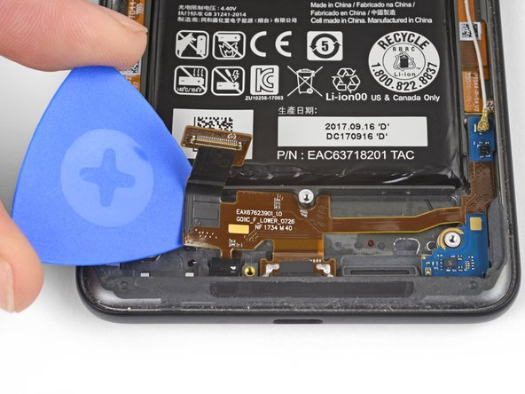 Starting from the left side, slide an opening pick under the charging assembly flex cable to separate it from the phone case.