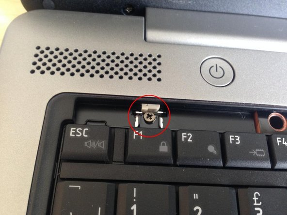 Remove a screw retaining the keyboard.