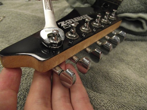 Using the 10mm wrench, remove the hollow hex bolts and washers from the tuning pegs.