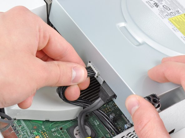 Grab the power connector by its cables and pull it straight out of its socket on the optical drive.