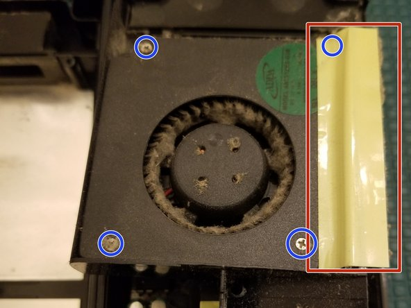 Remove tape in order to remove fan from its housing unit. This also uncovers a hidden screw.