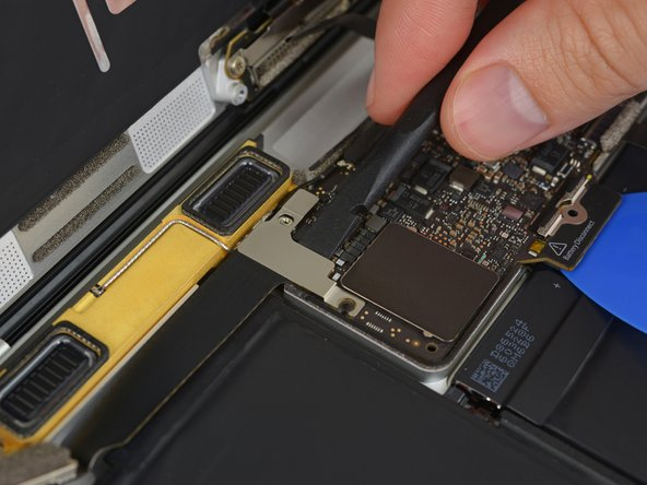 Use the flat end of a spudger to disconnect the USB-C port cable bracket by prying it straight up from the logic board.