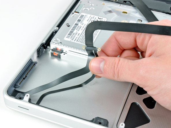Carefully peel up the thin IR sensor/sleep LED ribbon cable from the adhesive securing it to the upper case.