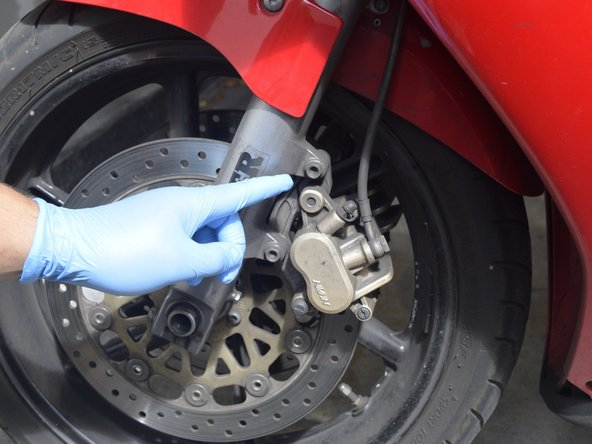The caliper is attached to the forks by two 12-mm hex bolts. Remove these bolts with a 12mm wrench.