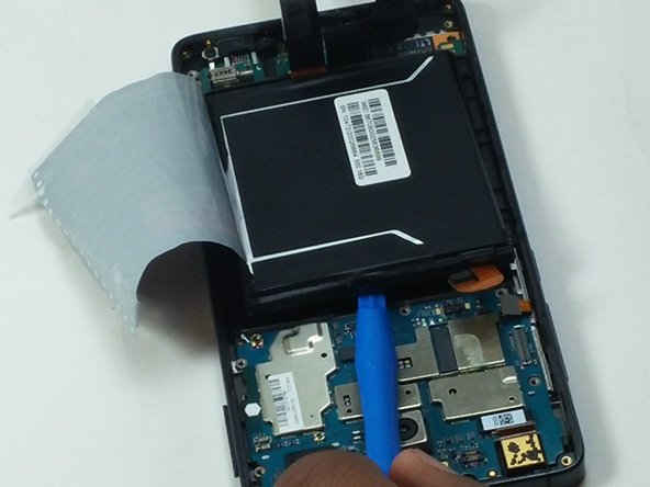 Use the plastic opening tool to gently pry the battery out of its casing for removal.