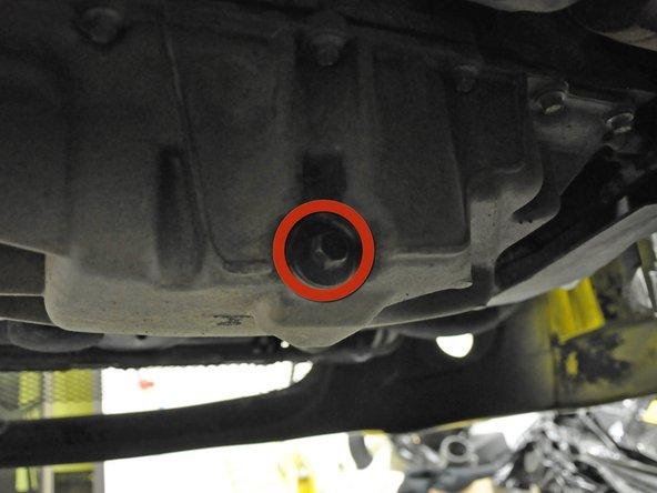 Suche die Ölablassschraube unter dem Auto. Diese hat einen 13 mm Sechskant und zeigt zur Rückseite des Fahrzeuges.