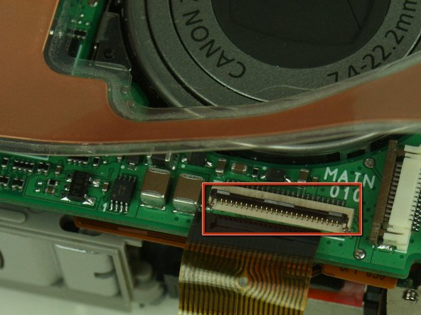 Locate the ribbon cable on the main circuit board, which sits below the lens.