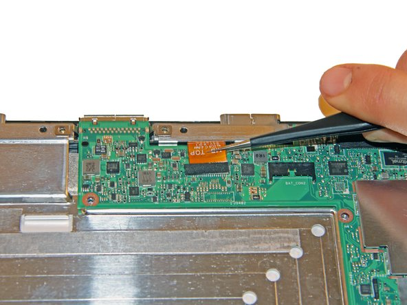 At the top end of the motherboard, use tweezers to gently slide the orange connection apparatus out of the connection port.
