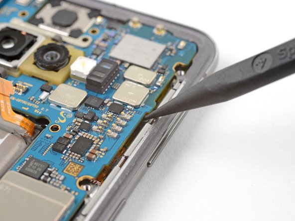 Insert the point of a spudger underneath the right edge of the motherboard, near the volume down button.