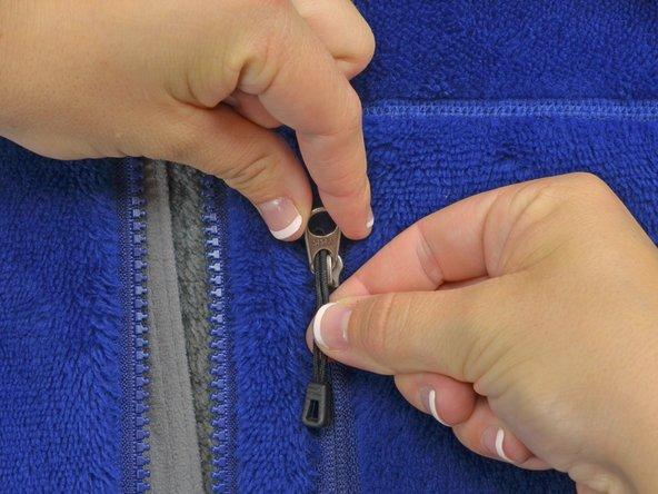 Den Anhänger in das kleinere Loch am Reißverschlussschieber einführen. Das ist das obere Loch, in dem der Anhänger üblicherweise eingehängt ist.